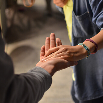 picture of two people reaching their hands out for each other